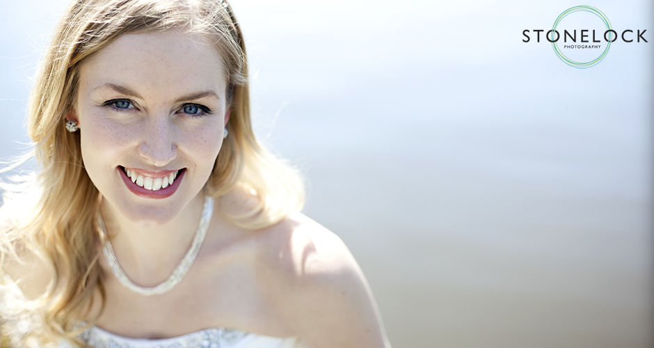 A bride sits by a river tightly cropped in gazes into the camera with a big smile