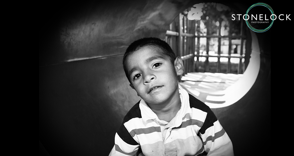 A young boy sits at the front end of a tunnel in a playground and stares into the camera