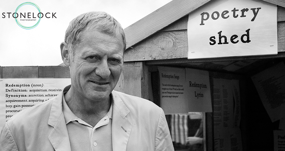 Poet laureate Andrew Motion stands in front of the poetry shed - a shed filled with poems - at Greenbelt Arts festival