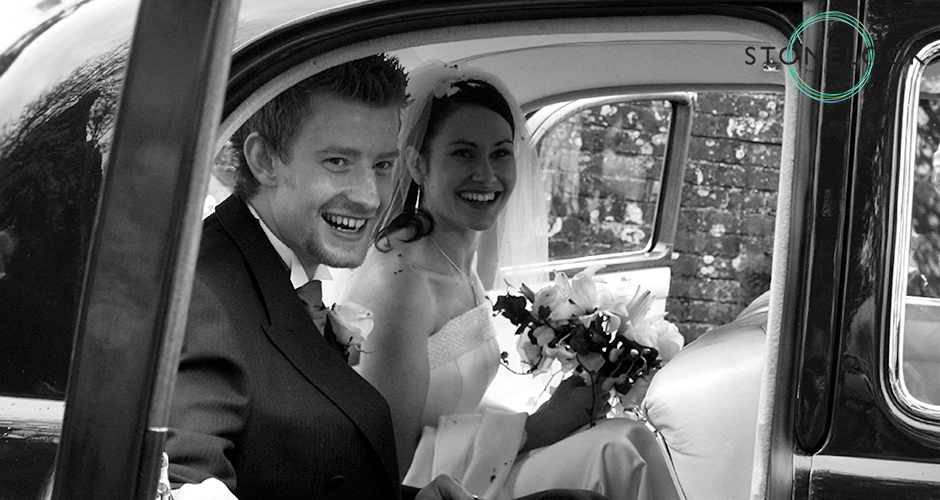 A just married bride and groom sit in their wedding car smiling