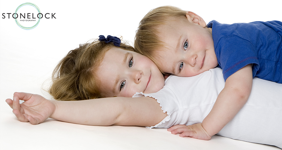Two children lie on the floor in a photography studio, the young boy giving his older sister a cuddle