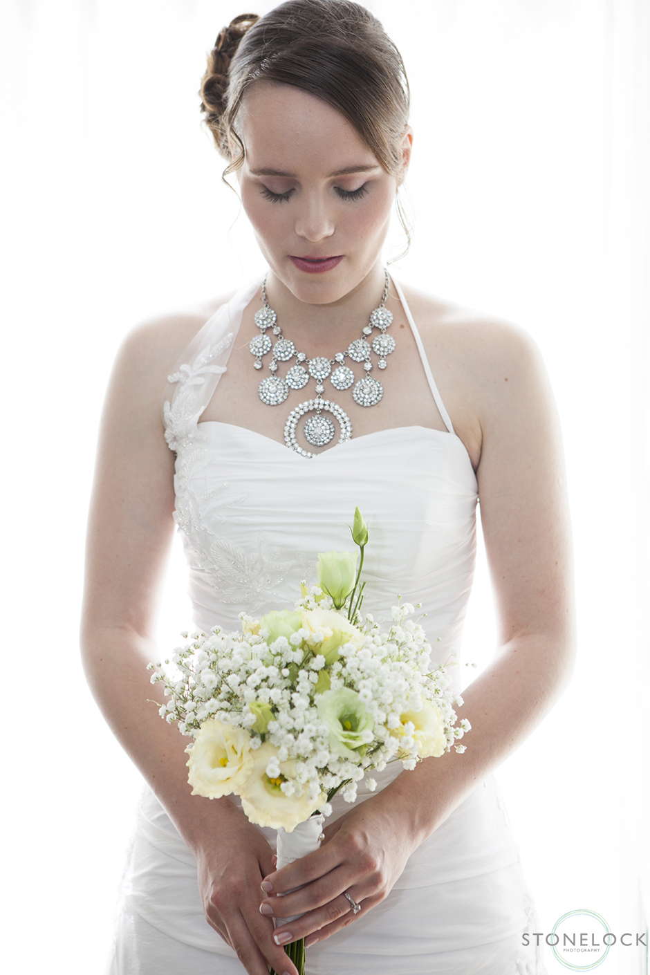 A photograph of a bride holds her flowers on her wedding day in front of a window, she is backlit and looks down at the flowers