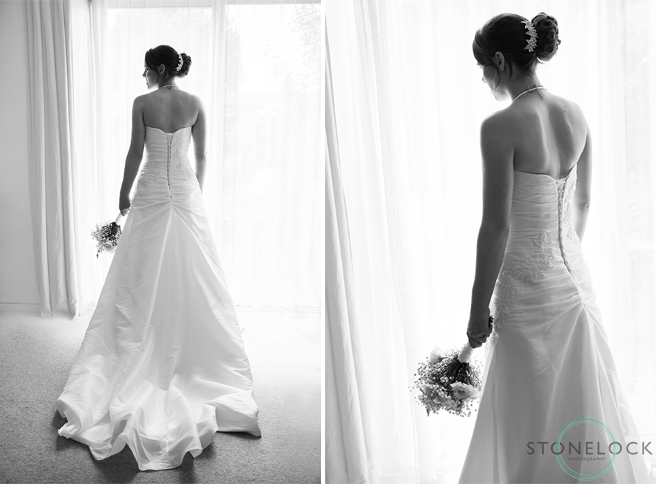 A photography of a bride looks out of the window on her wedding day whilst wearing her wedding dress, the train lays on the floor behind her, in black & white