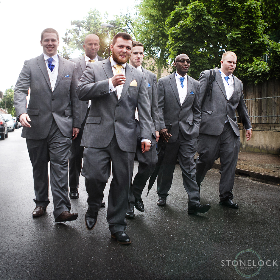 A groom his best man & ushers walk to the wedding ceremony in the style of reservior dogs