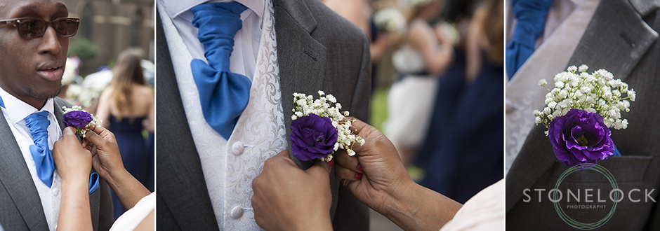 An usher at a wedding puts on his button hole with a little help, the flowers are purple and white