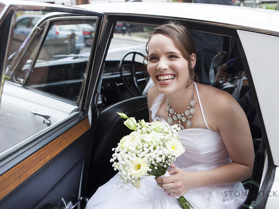A bride arrives in the wedding car at the wedding ceremony with a big smile on her face, at Mitcham Lane Baptist Church