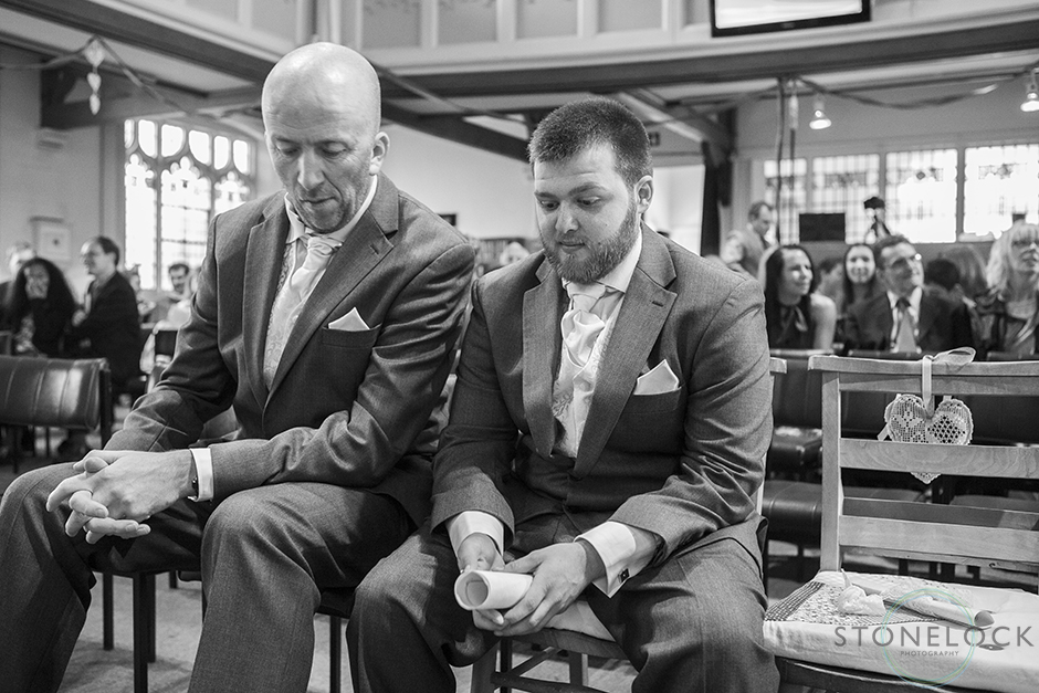 The groom waits nervously at the from of the church for the bride to arrive, the best man gives him words of wisdom, black and white