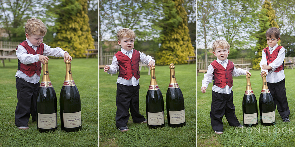 The page boys stand next to a large bottle of champagne at the wedding reception, the bottles are nearly as tall as the boys