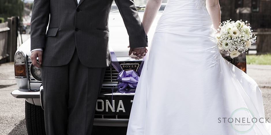 The bride and groom lean on the front of the wedding car at Mitcham Lane Baptist Church