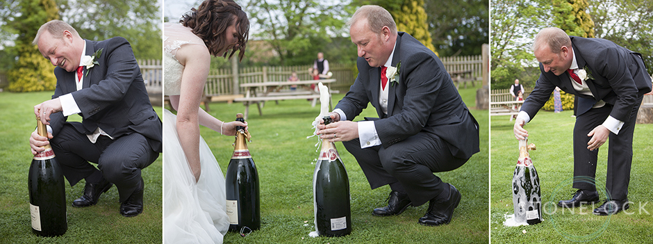 The groom opens a large bottle of champagne at the wedding reception