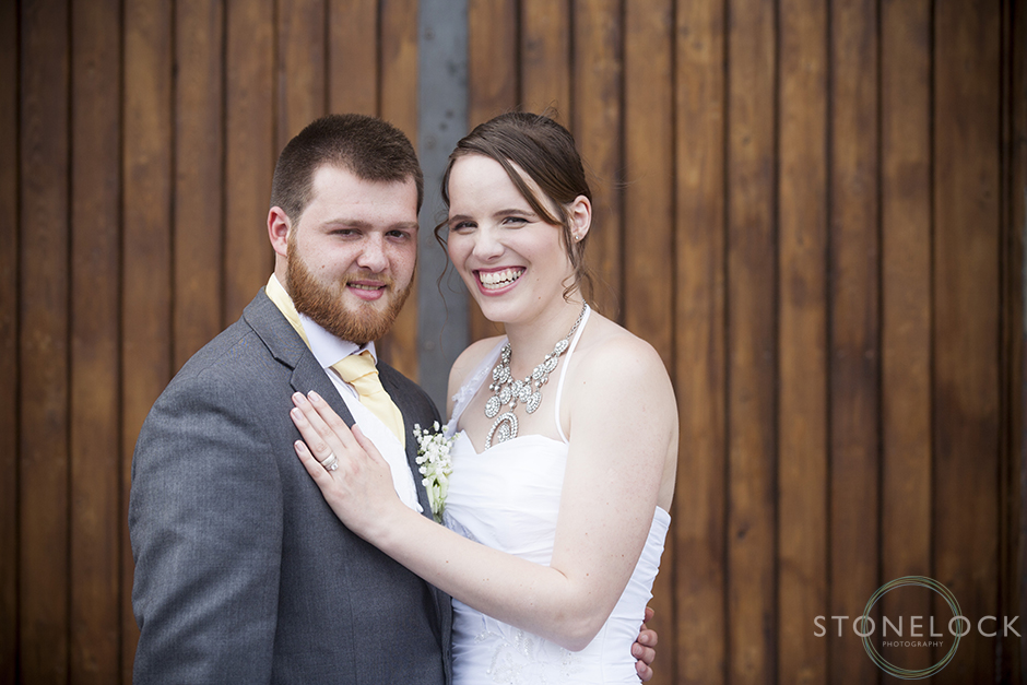 The bride and groom pose in front of a wooden door