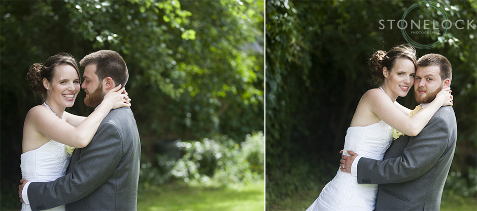 The bride wraps her arms around the groom as they stand in front of a background of greenery