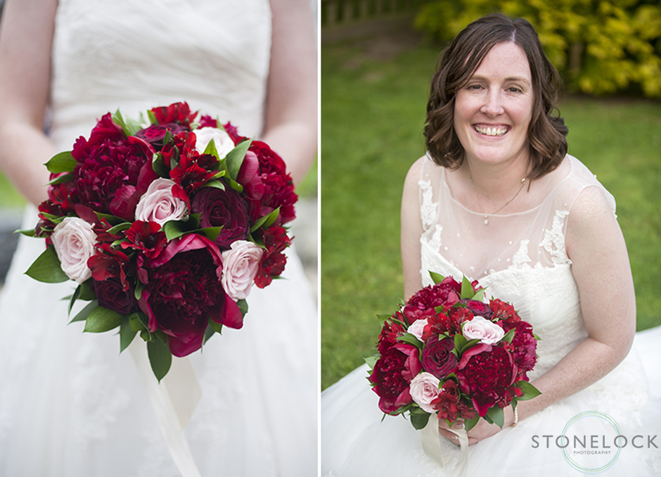 The bride poses with her red flower bouquet