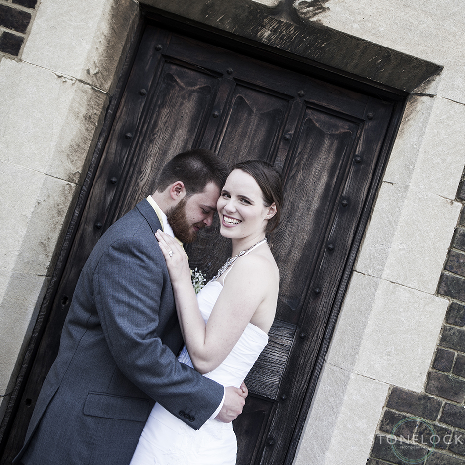 The bride and groom pose outside a wooden door, the photos is cropped at an angle and the groom rests his head on the brides head