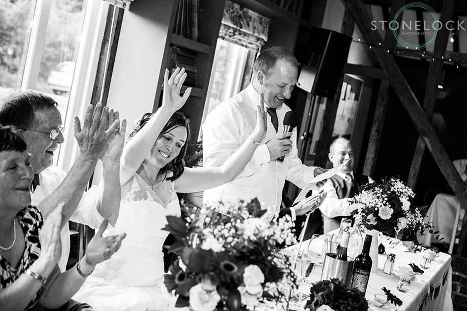 The bride cheers the groom as he gives his wedding speech shot in black and white