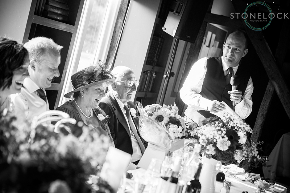 The mother of the groom laughs during the wedding speeches shot in black & white