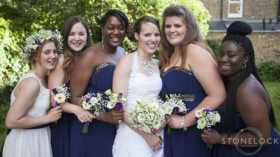 The bride with her bridesmaids leaning in close