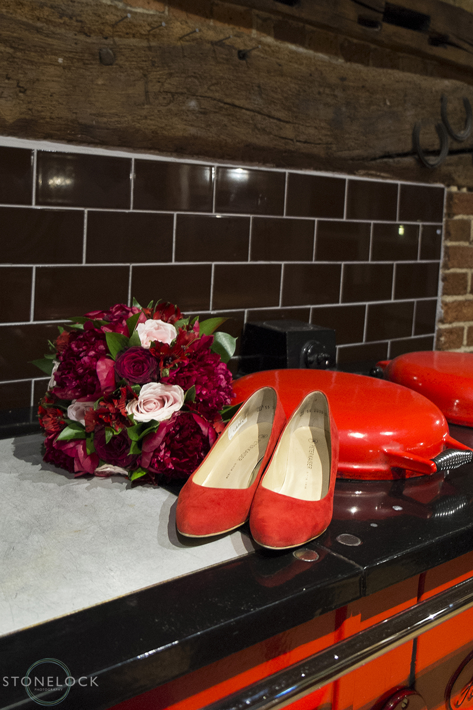 A brides red wedding shoes sit with her red flowers on a red age oven at the red barn in Surrey