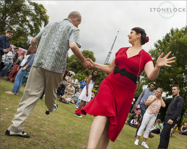 A lady in red from the dance company Swing Patrol swing dances in Crystal Palace Park as part of the Crystal Palace Overground Festival and Vintage up the Palace
