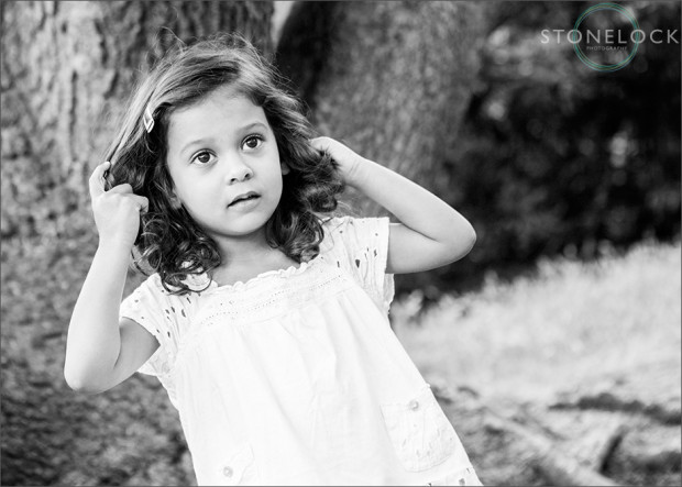 Family photo shoot in Coombe Wood, Croydon. A young three year old girl plays with her hair and looks away from the camera, there is a large tree in the background and the photo is in black and white