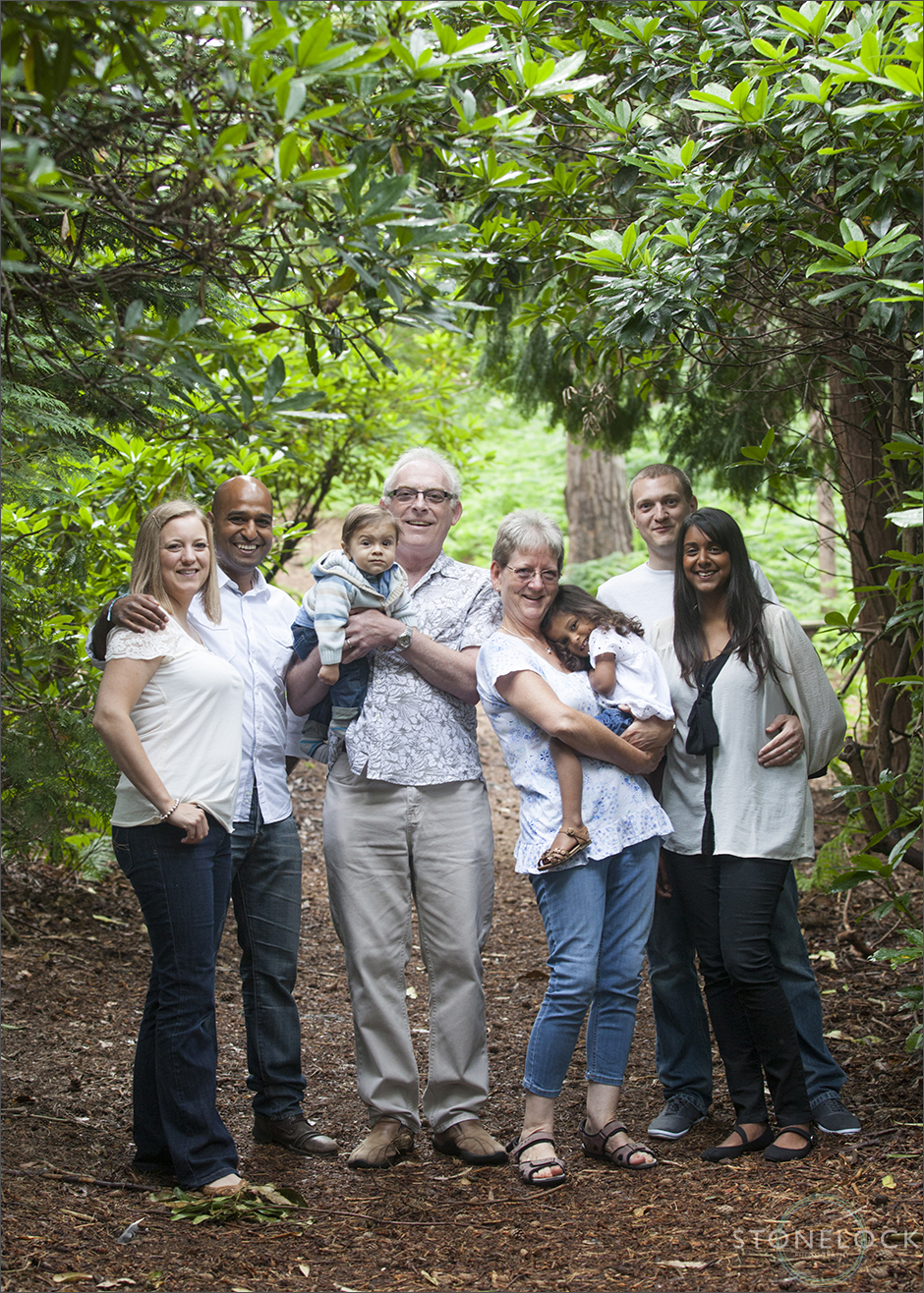 A family photo shoot in Coombe Wood, Croydon with grandparents, adult children and grandchildren. The family stand in the wood, amongst the trees