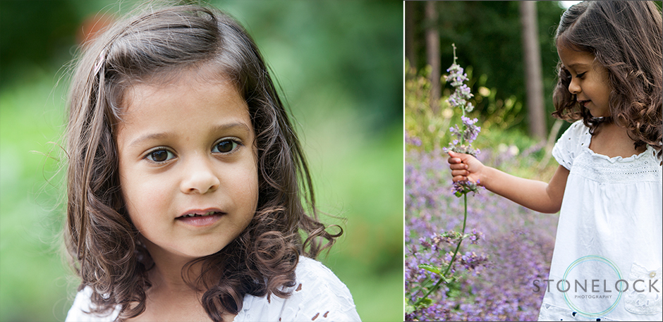 A three year old girls poses of r a photo at a family photo shoot in Coome Wood Croydon, she then picks some lavender from the flower bed