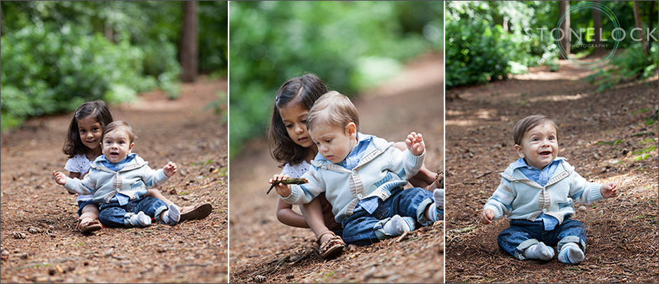 Two cousins, a girl of three and a baby of nine months sit on the ground in Coombe Wood, Croydon, London. The baby is supported between the girls lets and she is looking after him, the ground is wood chips with the trees in the background
