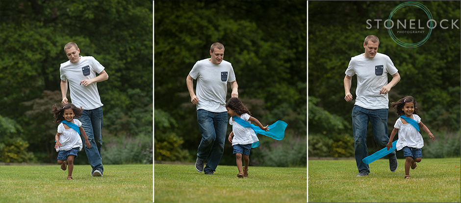 A man chases after his young niece in Coombe Wood, Croydon, the grass is green and there are dark green trees in the background