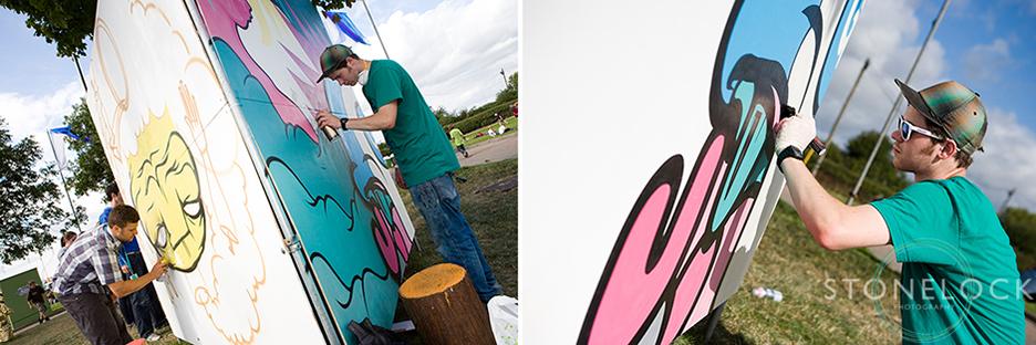A graffiti artist paints on a board at Greenbelt Arts Festival