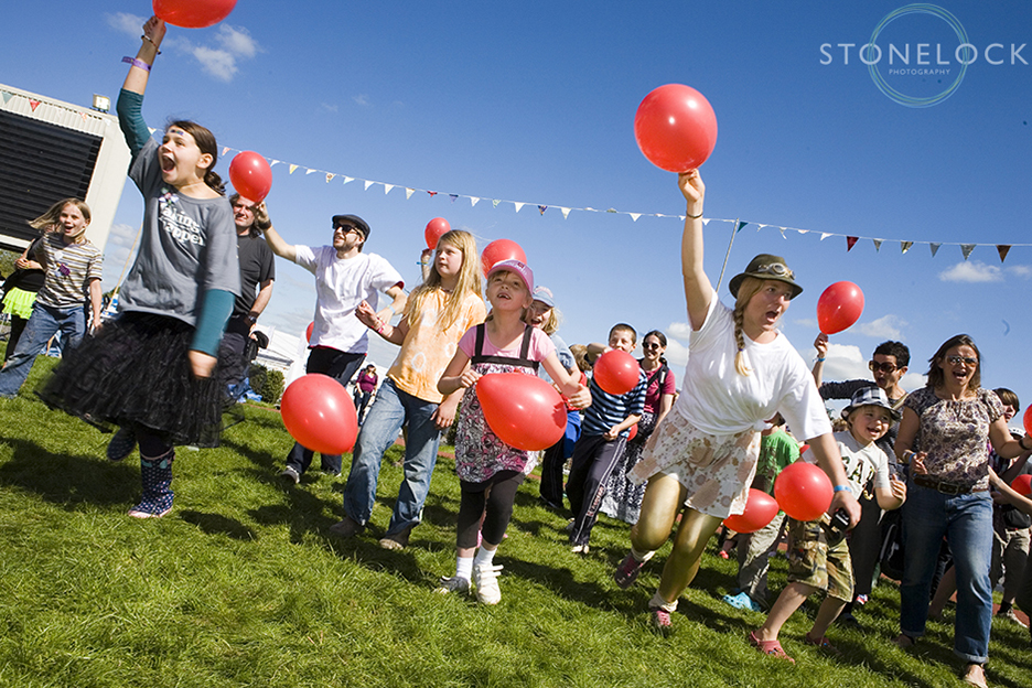 Balloon games in the Arena at Cheltenham Racecourse during Greenbelt Arts Festival, a group of participants run towards the camera holding bright red gallons that stand out well against the blue sky