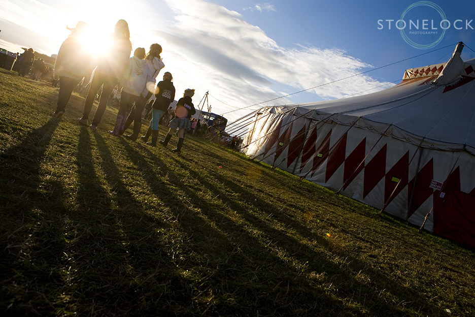 A group of people walk into the setting sun outside the big top tent at Greenbelt Arts Festival held at Cheltenham Racecourse