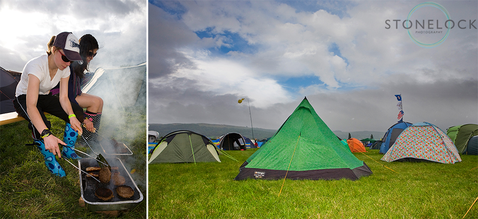 The campsite at Greenbelt Arts Festival, two people are cooking their dinner on a disposable bar-b-que against a backdrop of tents