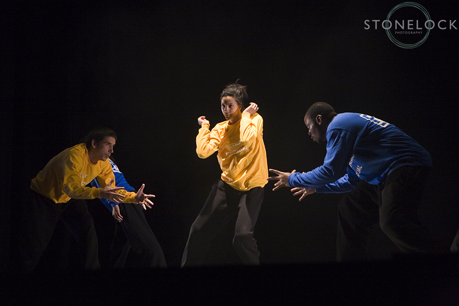 A dance performance at Greenbelt Arts Festival. The stage is completely black and so the dancers in yellow and blue stand out brightly against the backdrop