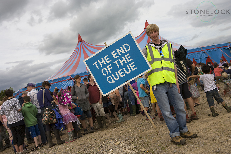 A steward stands outside a big top tent at Greenbelt Arts Festival holding a sign that says the end of the queue