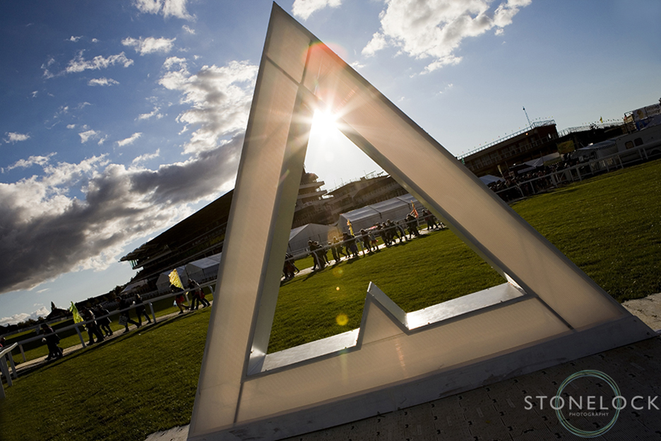 The sun shines through a sculpture of the Greenbelt logo at Cheltenham Racecourse at the Greenbelt Arts Festival