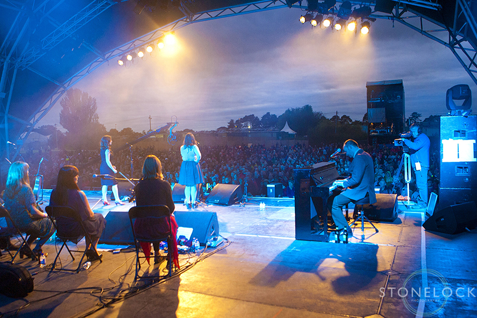 A photograph shot from the back of MainStage at Greenbelt Arts Festival looking our over the crowds listening to The Unthanks perform at dusk