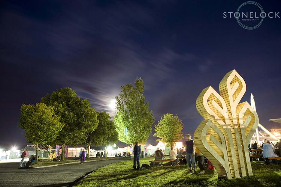 The Greenbelt Arts Festival sculpture shot at night time with a slow shutter speed to show movement of people and clouds in the sky