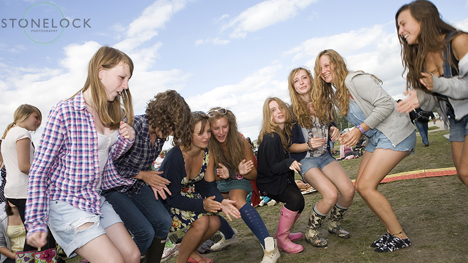 A group of girls dancing to music at Greenbelt Arts Festival at Cheltenham Racecourse