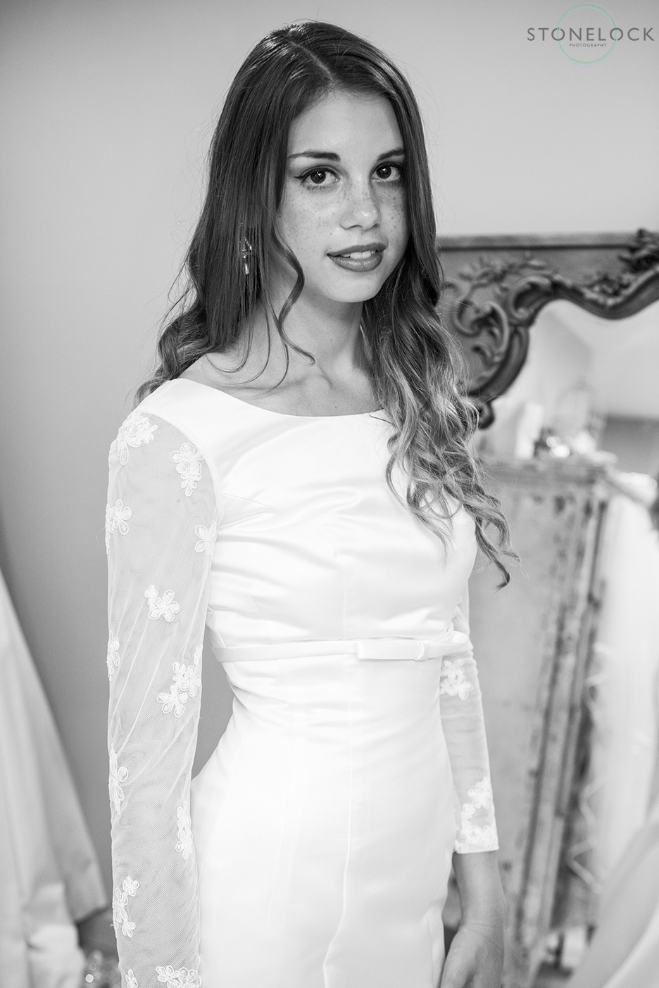 A model wears Lou Lou emilia, long sleeve wedding dress at Helena Fortley Bridal Boutique in Caterham, Surrey. The photo is in black and white.
