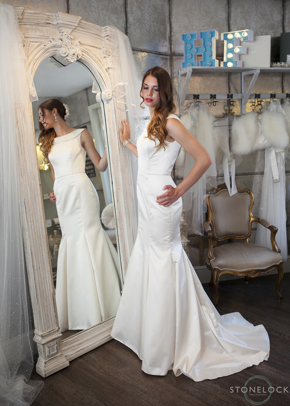 A model stands in front of a floor length mirror wearing Paloma Blanca 4414 wedding dress at Helena Fortley Bridal Boutique in Caterham