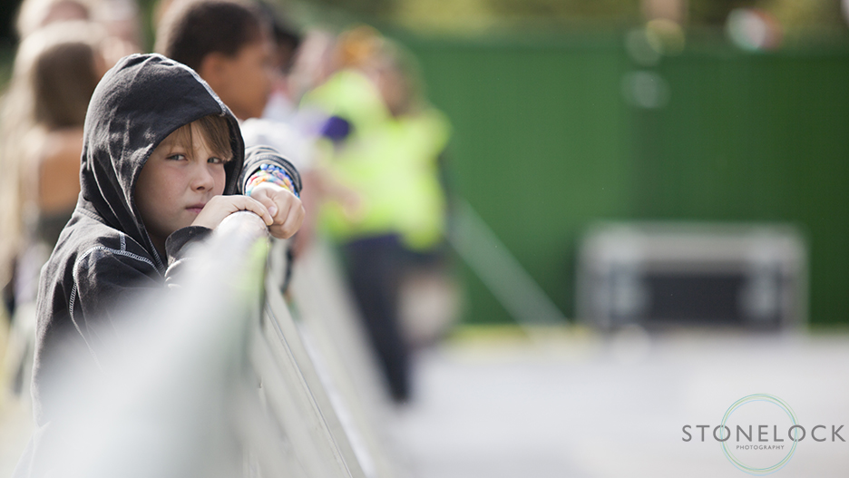 A small boy peers over the barrier at MainStage at Greenbelt Arts Festival