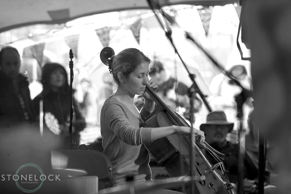 Shot in Black and White a girl plays the cello at the Canopy Stage at Greenbelt Arts Festival. The venue is an open sided tent, through in the background you can see the sunlit outside