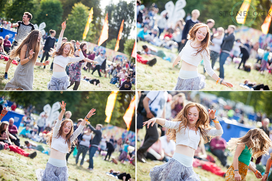 A girl dances at on the grass by MainStage at Greenbelt Arts Festival with the sun behind her, she is into the music and having a good time