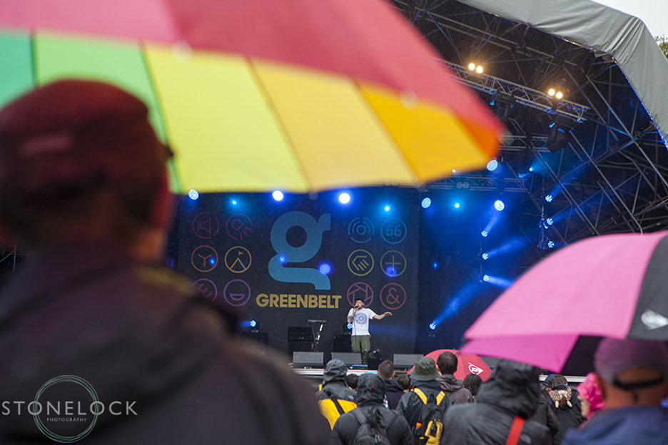 A man stands in the rain with a large rainbow umbrella watching Hobit perform on MainStage at Greenbelt Arts Festival. Shot from behind the man and his umbrella frame the artiste.