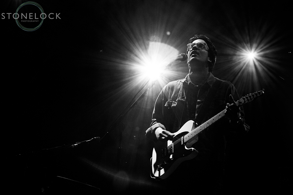 Luke Sital-Singh performs on stage at Greenbelt Arts Festival. Shot in black and white he looks up as he is playing his guitar, lights shine in the background.