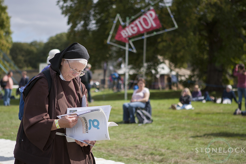 A nun reads the festival program in front go the Big Top venue at Greenbelt Arts Festival at Boughton House