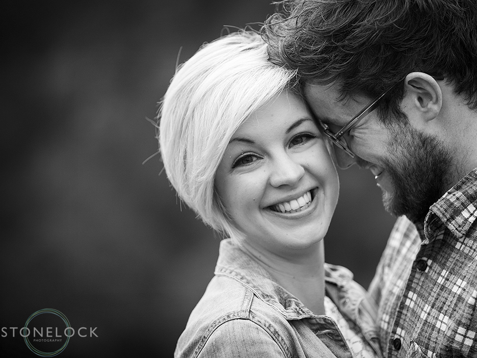 A man leans his head onto his girlfriend's during an engagement shoot in Bristol, the photo is in black and white