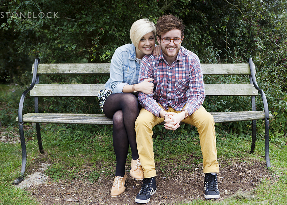 The couple sit on a bench on the Downs in Bristol during their engagement shoot, the girl has her arms interlinking with the guy