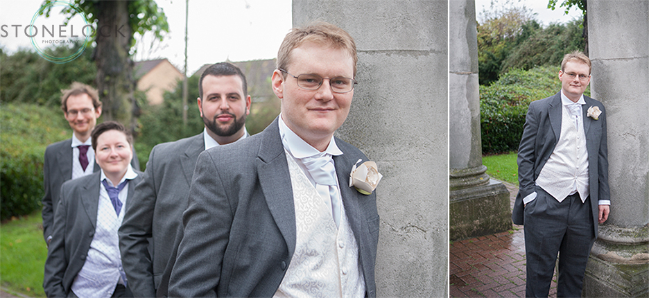 The groom and groomsmen pose for photos before the wedding. They lean against concrete posts.