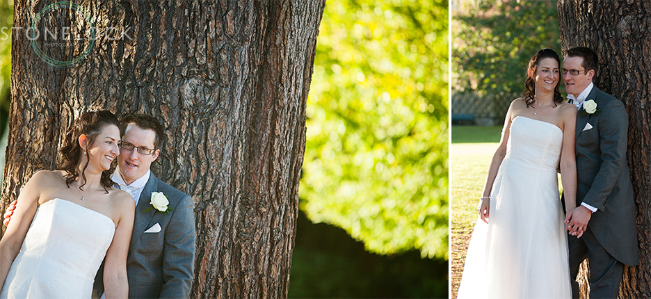 The bride and groom pose for portraits in front of a huge oak tree at Bourne Hall in Ewell village